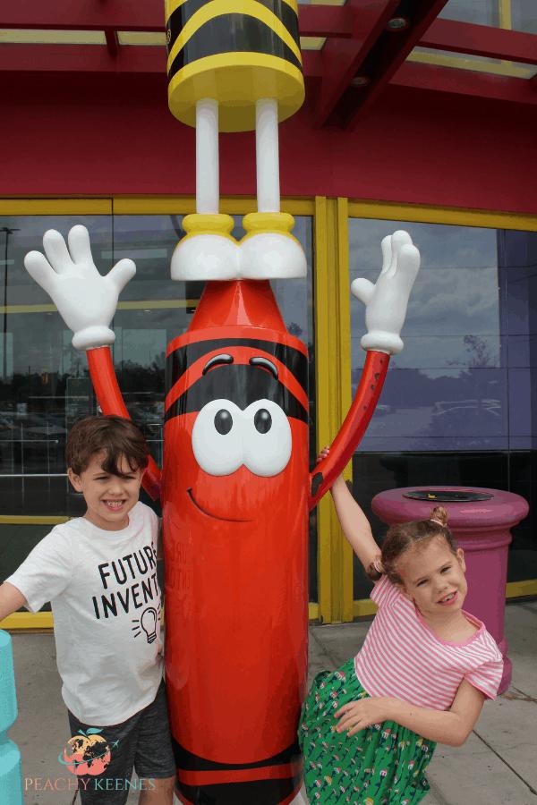 Children standing next to Crayola crayon statue