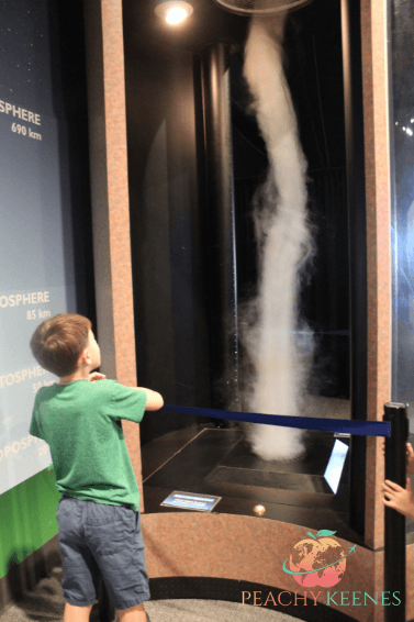 Boy looking at a tornado at the Orlando  indoor activity-Orlando Science Center