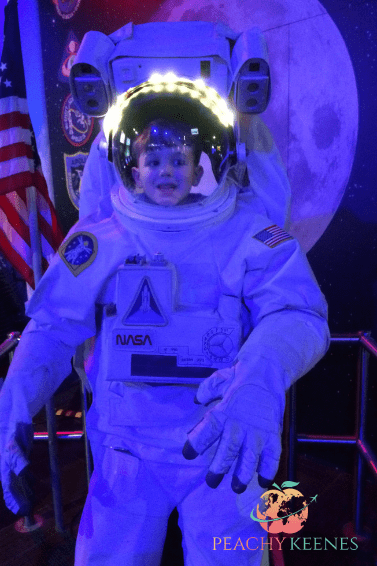 A picture of my son in an astronaut costume at Wonderworks Orlando.  A perfect indoor activity in Orlando.