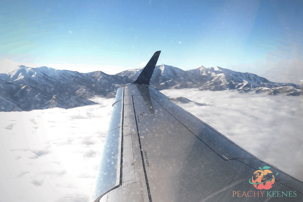 Picture of plane wing with mountains in the background