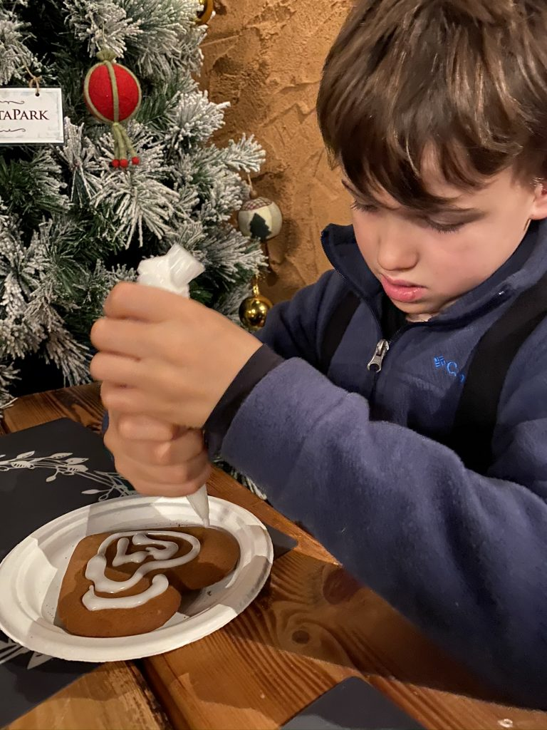 child decorating gingerbread heart