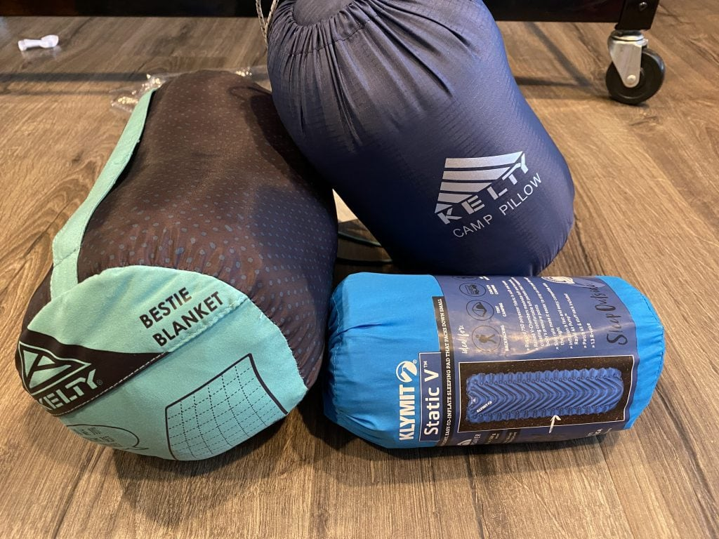 Family camping gear: blanket, sleeping bag, and mat