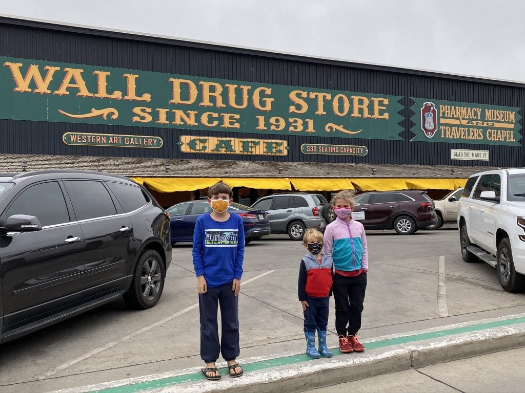 children standing in front of wall drug store
