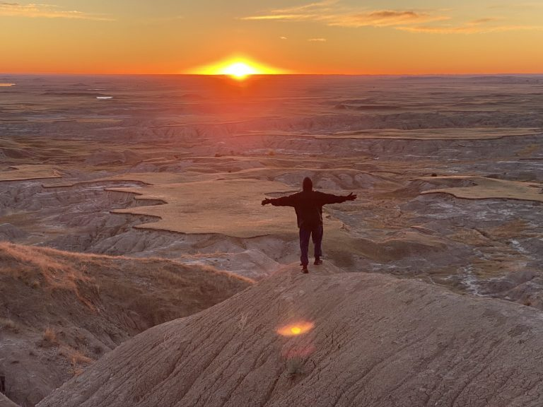 Man standing with arms out as sun comes up over the Badlands National Park