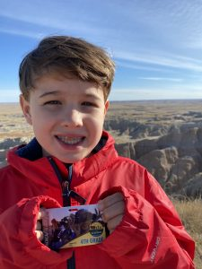 Boy holding Every Kid Outdoors 4th grade National Park pass